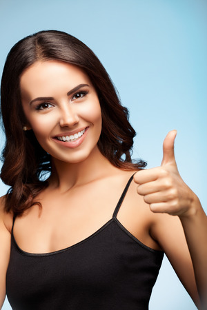 Portrait of beautiful cheerful happy smiling young brunette woman showing thumb up hand sign gesture, over bright blue background