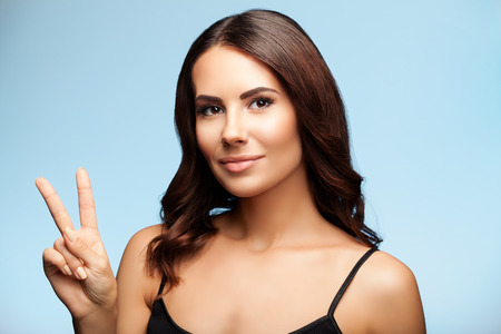 Beautiful young brunette woman in black tank top clothing, showing two fingers or victory gesture, on bright blue background