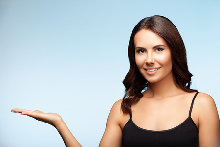 Young happy smiling brunette woman in black casual clothing, showing something or empty copyspace area for slogan or advertising text message, on bright blue background