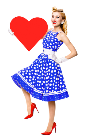 Full body of happy woman holding heart symbol, dressed in pin-up style blue dress with polka dot, isolated over white background. Caucasian blond model in retro fashion and vintage concept studio shoot. Banque d'images