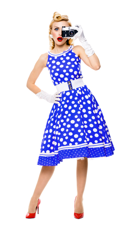 Full body portrait of young woman with no-name old film camera, taking picture, dressed in pin-up style blue dress in polka dot. Caucasian blond model posing in retro fashion and vintage concept studio shoot, isolated over white background.