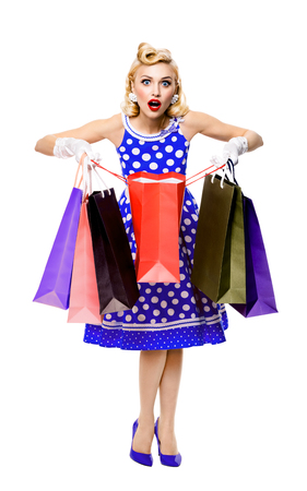 Full body portrait of woman in pin-up style blue dress in polka dot holding shopping bags, isolated on white background. Caucasian blond model posing in sales, consumer, retro fashion and vintage concept.