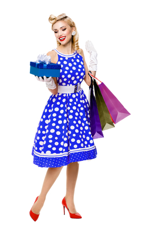 Full body portrait of woman in pin-up style blue dress in polka dot holding gift box and shopping bags, isolated on white background. Caucasian blond model posing in sales, consumer, retro fashion and vintage concept. Banque d'images