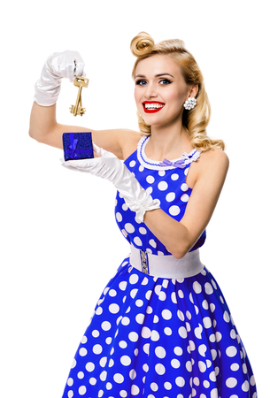 Happy smiling blond woman in pin-up style blue dress in polka dot, showing keys from new house, isolated over white background. Caucasian model posing in retro fashion, vintage and real estate concept.