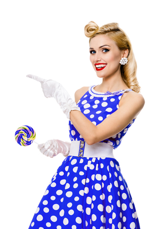 Happy smiling blond woman in pin-up style blue dress in polka dot, showing something or empty copyspace area for text, slogan or advertising message, isolated over white background. Caucasian model posing in retro fashion and vintage concept.