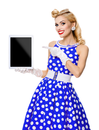 Happy smiling woman, showing blank no-name tablet pc monitor, with copyspace, dressed in pin-up style blue dress in polka dot, isolated on white background. Caucasian blond model posing in retro fashion vintage concept.