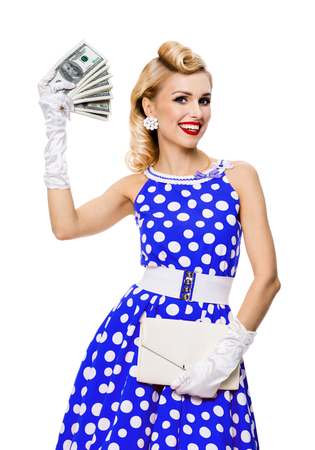 Portrait of beautiful young happy smiling woman with money cash, dressed in pin-up style blue dress in polka dot. Caucasian blond model posing in retro fashion and vintage studio concept, isolated over white background.