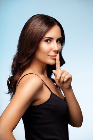 Portrait of beautiful young brunette woman with finger on lips, on bright blue background Stock Photo