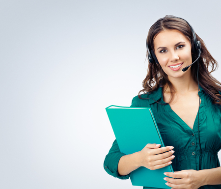 Portrait of happy smiling cheerful beautiful female support phone operator in headset, green confident clothing with folder, empty copyspace area for slogan or advertising text message, over grey background. Call center and customer support service concept.