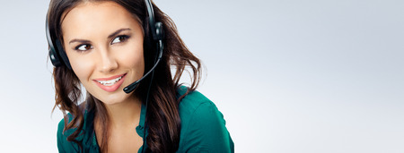 Portrait of happy smiling cheerful beautiful female phone operator in headset, green confident clothing, empty copyspace area for slogan or advertising text message, over grey background. Call center and customer support service concept. Stock Photo