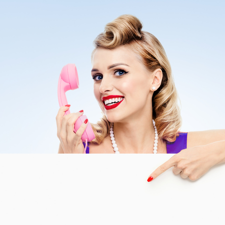 Woman with phone, in pin-up style dress, showing blank signboard  with copyspace area for slogan or advertising text message, on blue background. Caucasian blond model in retro fashion and vintage concept. Banco de Imagens
