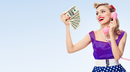 Happy woman with money, talking on phone, dressed in pin-up style dress, with copyspace area for slogan or advertising text message, on blue background. Blond model in retro fashion and vintage concept. Banco de Imagens
