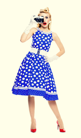 Full body portrait of young woman with no-name old film camera, taking picture, dressed in pin-up style blue dress in polka dot. Caucasian blond model posing in retro fashion and vintage concept studio shoot, over yellow background.