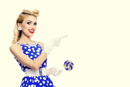 Happy smiling blond woman in pin-up style blue dress in polka dot, showing something or empty copyspace area for text, slogan or advertising message, over yellow background. Caucasian model in retro fashion and vintage concept.