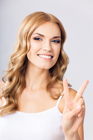 Happy smiling beautiful young blond woman showing two fingers or victory gesture, over grey background Stock Photo