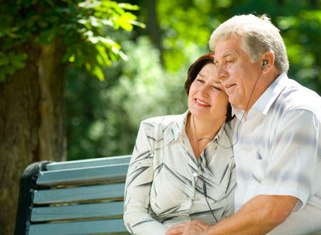 Happy smiling cheerful senior couple listening music or audio book in headset or praying together, outdoors Stock Photo