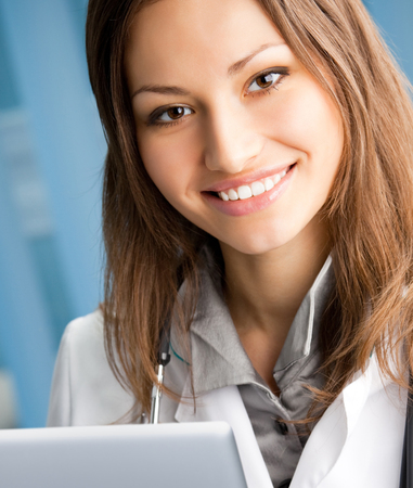 Portrait of cheerful female doctor working with laptop at office Stock Photo