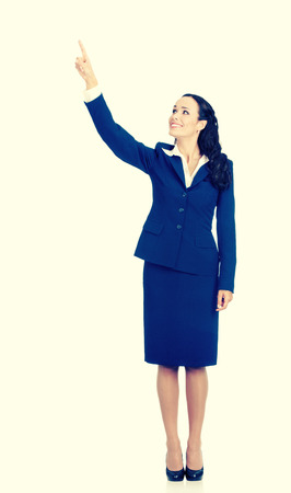 Full body of happy smiling young beautiful business woman in blue confident suit, showing up on something or copyspace area for product or sign text, isolated over yellow background