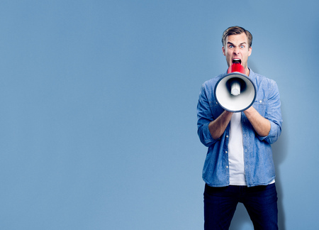 Man shouting through megaphone, with empty copyspace area for slogan, advertising or text message, over blue background. Caucasian male model smart casual clothing making announcement, studio concept.