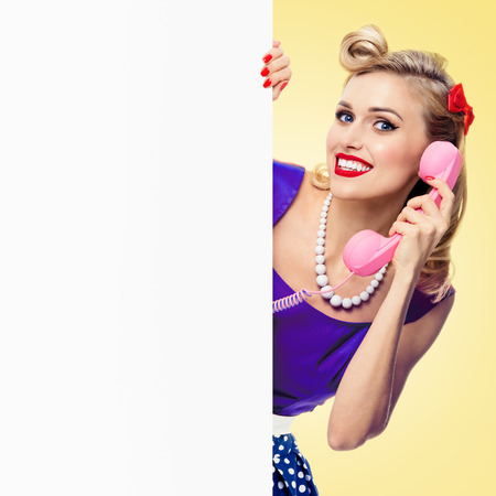 Woman with phone, in pin-up style dress, showing blank signboard with copyspace area, on yellow background. Caucasian blond model in retro fashion and vintage concept.