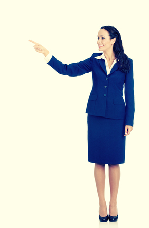 Full body of happy smiling young beautiful business woman in blue confident suit, showing on something or copyspace area for product or sign text, isolated over yellow background
