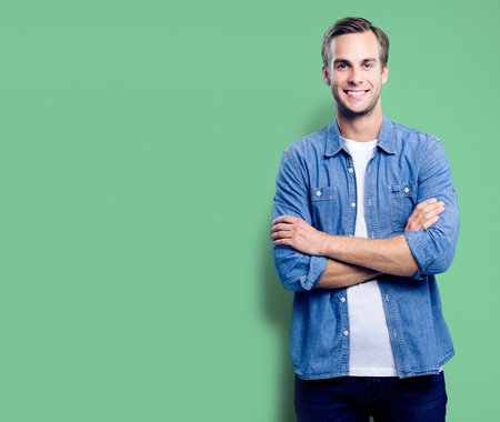 Portrait of happy smiling man standing in crossed arms pose, with empty copyspace area for slogan, advertising or text message, over green background. Caucasian male model in smart casual clothing, st