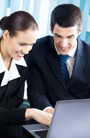 Two smiling young businesspeople working with laptop at office Stock Photo