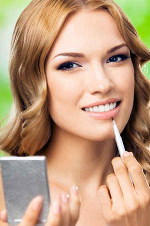 Portrait of young happy smiling woman with make up brush and mirror, outdoors Stock Photo