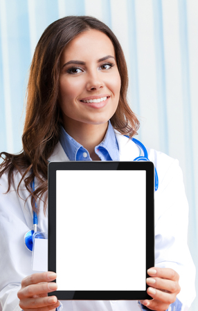 Portrait of happy smiling young female doctor showing blank tablet pc for copyspace, at office