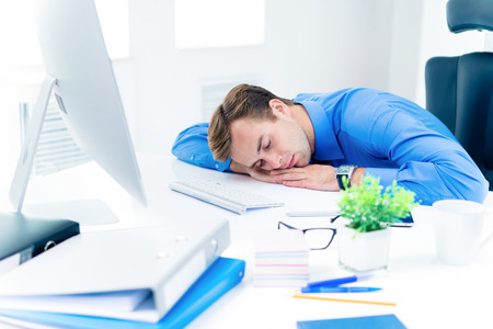 Tired businessman in blue shirt, sleeping at workplace, with desktop computer at office. Business, job and overworking concept.