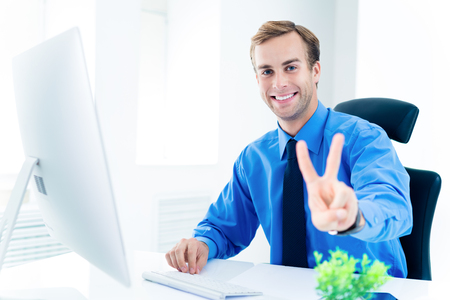 Portrait of happy smiling businessman in confident clothing, blue shirt and tie, showing two fingers or victory gesture, working with desktop computer at office. Success in business, job and education concept. Banque d'images