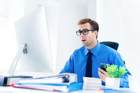 Shocked or surprised businessman in confident blue shirt and glasses, working with desktop computer at office. Success in business, job and education concept. Stock Photo