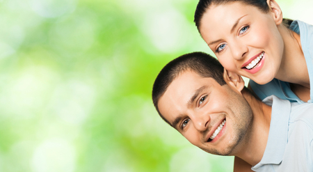 Young happy smiling attractive couple, outdoors. To provide maximum quality, I have made this image, by combination of three photos. You can use left part for slogan, big text or banner. Imagens