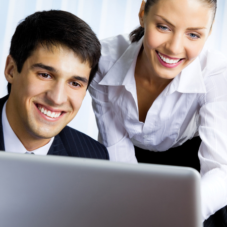Two smiling young businesspeople working with laptop at office 版權商用圖片