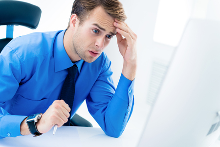 Shocked or surprised unhappy businessman in confident blue shirt and glasses, working with desktop computer at office. Business, job and education concept.