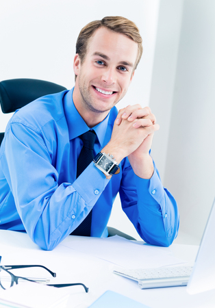 Portrait of young businessman in blue shirt and tie at workplace. Success in business, job and education concept shot. Imagens