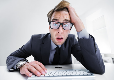 Tired or surprised young businessman in black suit, working with computer at office. Success in business concept. Stock Photo