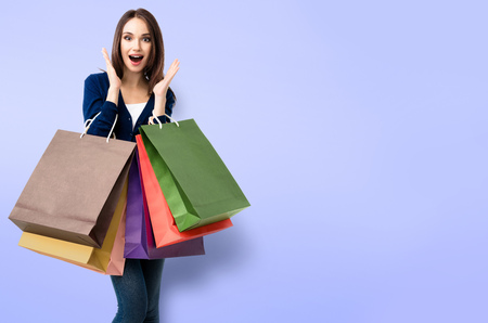 Very happy beautiful girl in blue casual clothing holding shopping bags, over violet background, with copyspace for some slogan, advertising or text message.