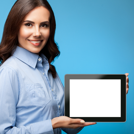 Happy smiling attractive young businesswoman showing blank no-name tablet pc monitor, on blue background, with copy space for some text, advertising or slogan Banque d'images - 115400607