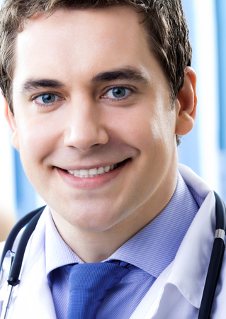Portrait of happy smiling doctor at office Banque d'images - 115400609