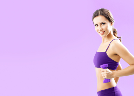 Young woman in fitness wear exercising with dumbbell, with copyspace for some text, advertising or slogan, against pink background Banque d'images - 115400613