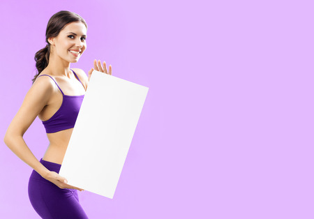 Cheerful young woman in fitness wear showing blank signboard with copyspace for some text, advertising or slogan, against pink background Banque d'images - 115400617