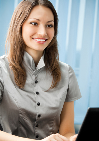Young cheerful smiling business woman working with laptop at office Banque d'images - 115400700