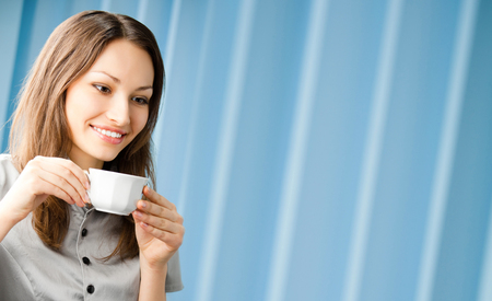 Cheerful smiling business woman drinking coffee at office, with copy space Banque d'images - 115400702