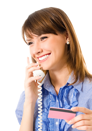 Young happy smiling business woman with plastic card, on cellphone, isolated on white background Banque d'images - 115400776