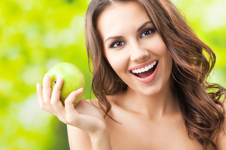 Portrait of young beautiful happy smiling woman with green apple, outdoors Banque d'images - 115400779