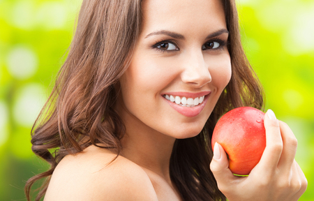 Young happy smiling woman with apple, outdoors Banque d'images - 115400781