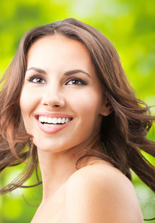 Portrait of beautiful young happy smiling woman with long hair, outdoors Banque d'images - 115400783