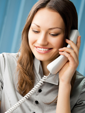 Young cheerful business woman with phone writing at office Banque d'images - 115400791