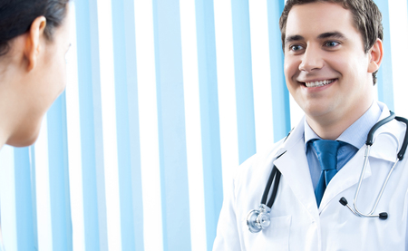 Portrait of cheerful smiling male doctor and female patient, with copyspace Banque d'images - 115400875